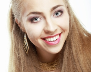 Young woman smiling and showing straight white teeth