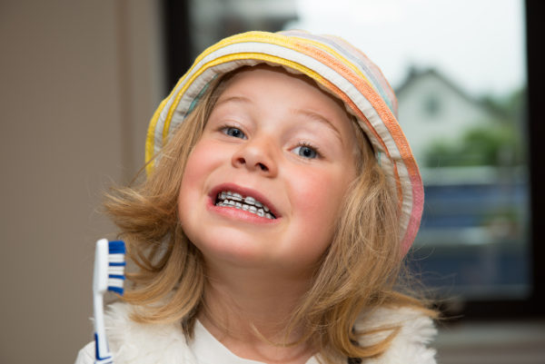 little girl with braces retainer and toothbrush