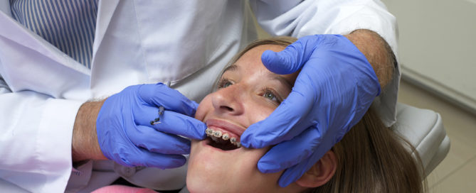 smiling girl having her braces checked by orthodontist