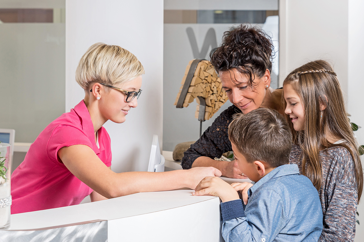 mother and kids checking into orthodonstist