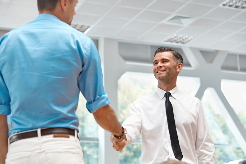 orthodontist greeting male invisalign patient